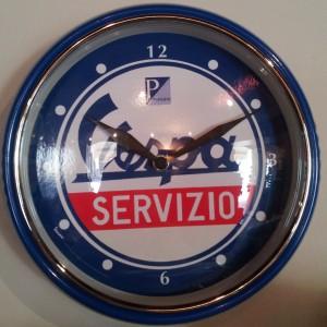 Orologio da parete Vespa Piaggio con ampia ghiera metallica colorata coerente con i colori dell'immagine interna. Il vetro è bombato. Diametro 23 cm.